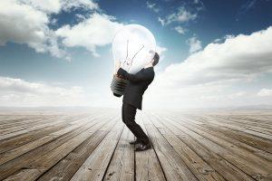 business man holding a huge bulb lamp