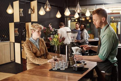 Un camarero sirviendo una taza de café en un bar.